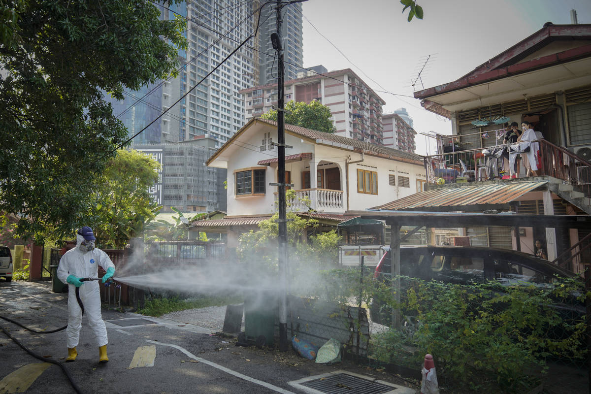 Health official spray disinfectant on Kampung Baru, a traditional Malay village in Kuala Lumpur ...