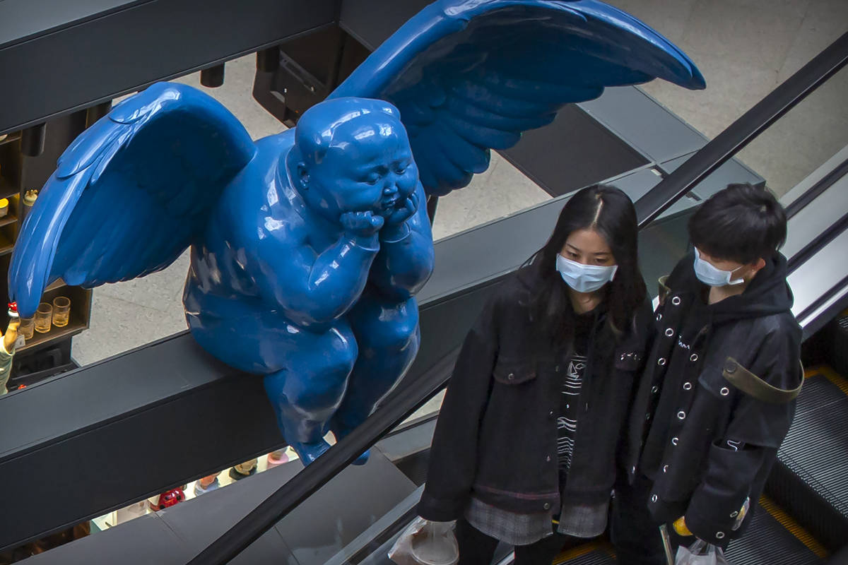 People wearing face masks ride an escalator near a winged statue at an upscale shopping mall in ...