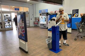 A customers grabs sanitizing wipes at Walmart Supercenter at 3950 W. Lake Mead Blvd. in North L ...