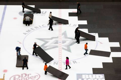 Crews cover the ice at American Airlines Center in Dallas, home of the Dallas Stars hockey team ...