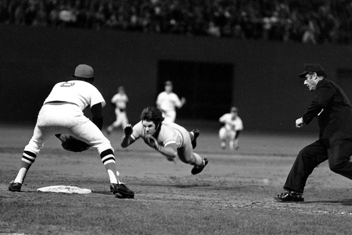 Pete Rose of the Cincinnati Reds is shown diving into third base in the ninth inning of Game 7 ...