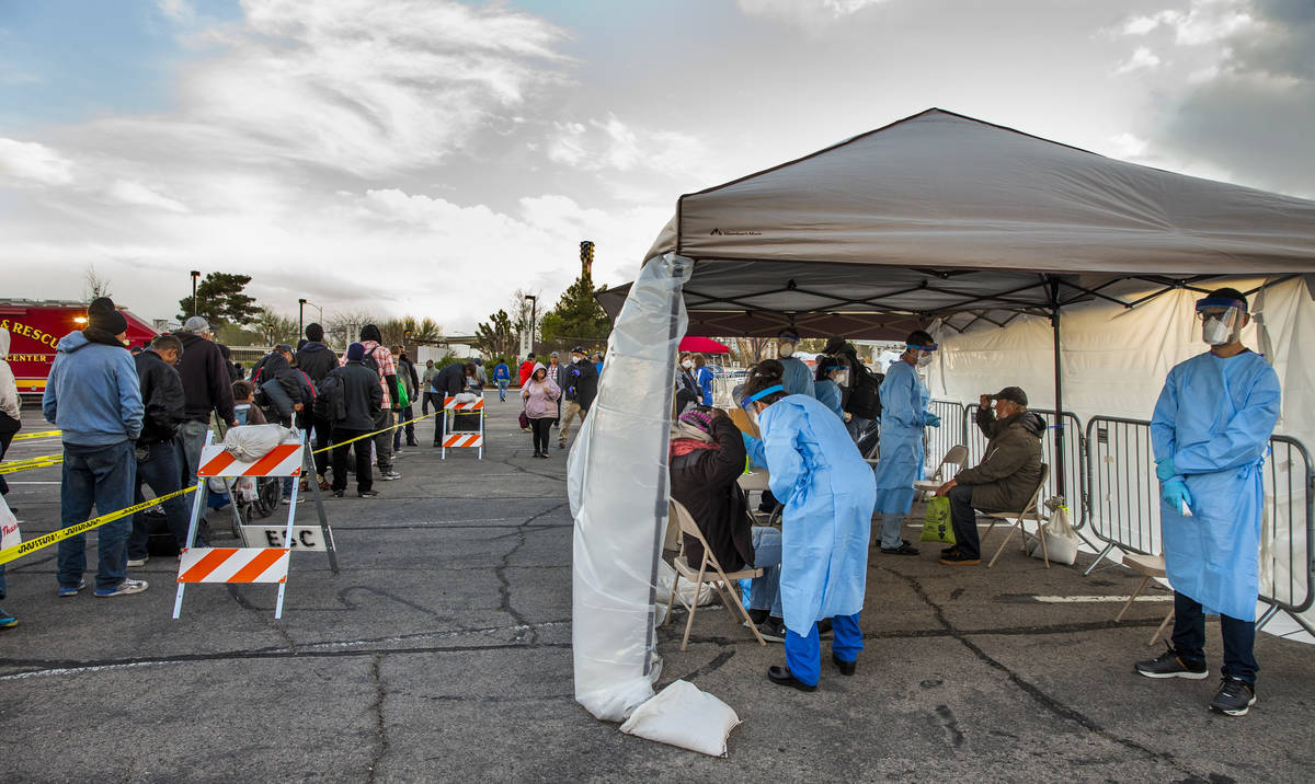 Touro University Nevada medical students, right, screen the homeless as they enter the temporar ...