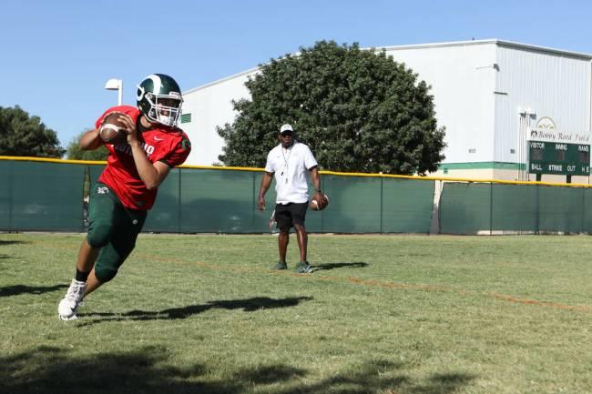 Rancho High School quarterback Ruben Vasquez runs with the football during a practice on a base ...