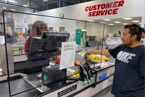 Cashiers work behind barriers at WinCo Foods at 7501 Washington Ave. in Las Vegas Tuesday, Marc ...