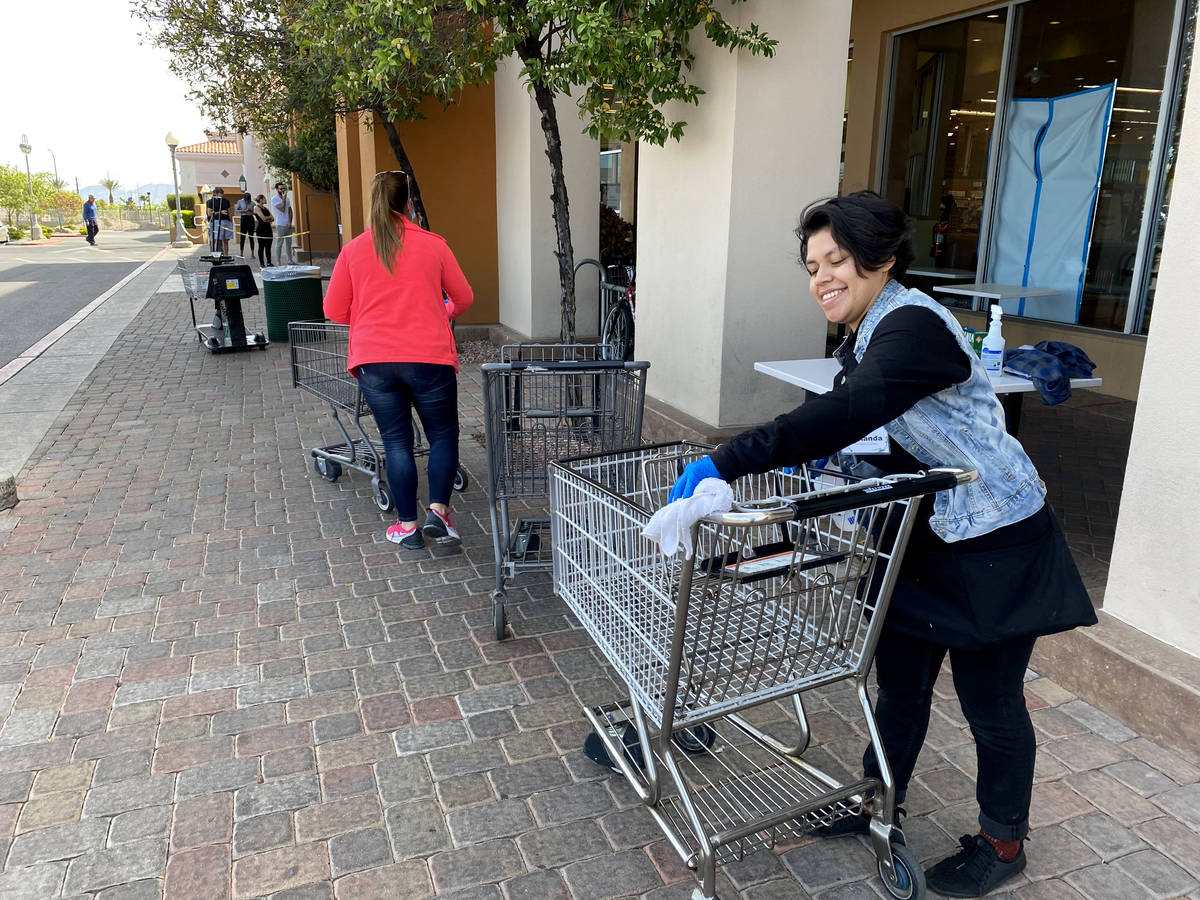 A worker sanitizes carts at Whole Foods at 8855 W. Charleston Blvd. in Las Vegas Tuesday, March ...