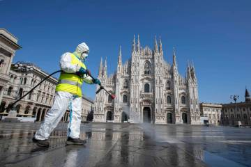 A worker sprays disinfectant to sanitize Duomo square, as the city main landmark, the gothic ca ...