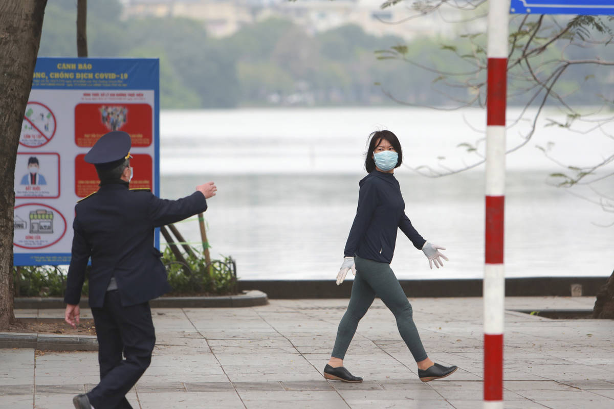 A security officer talks to a woman walking on a street in Hanoi, Vietnam, Wednesday, April 1, ...