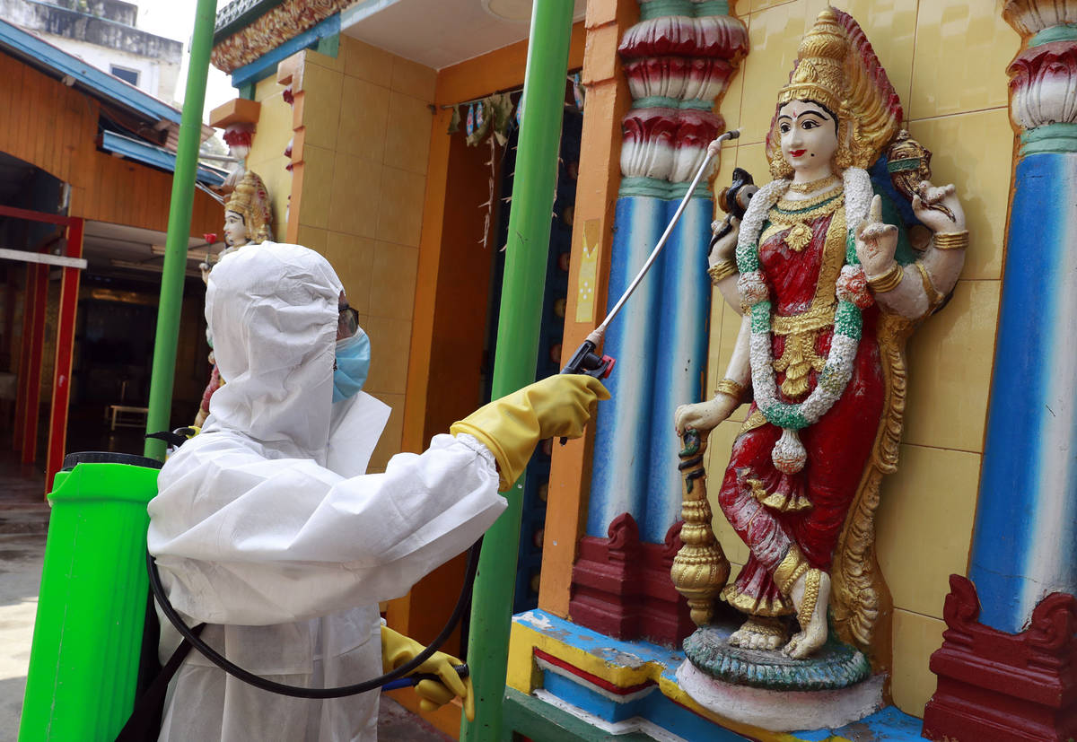 A member of the military wearing full protective gear sprays disinfectant at a Hindu temple to ...