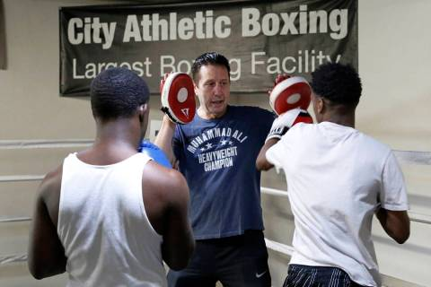 Armin Van Damme, owner of City Athletic Boxing, center, works with youth from the Spring Mounta ...