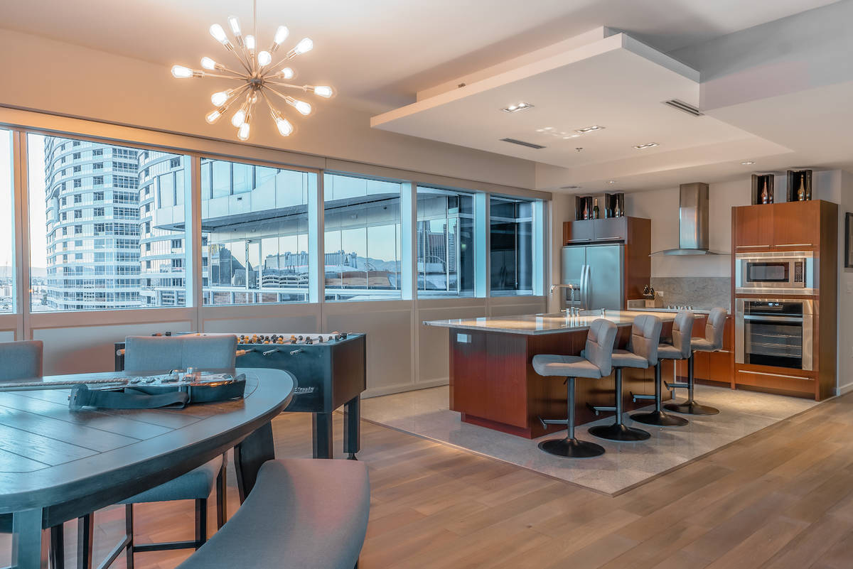 The kitchen and dining room face a floor-to-ceiling wall of glass with views of the Strip. (Red ...
