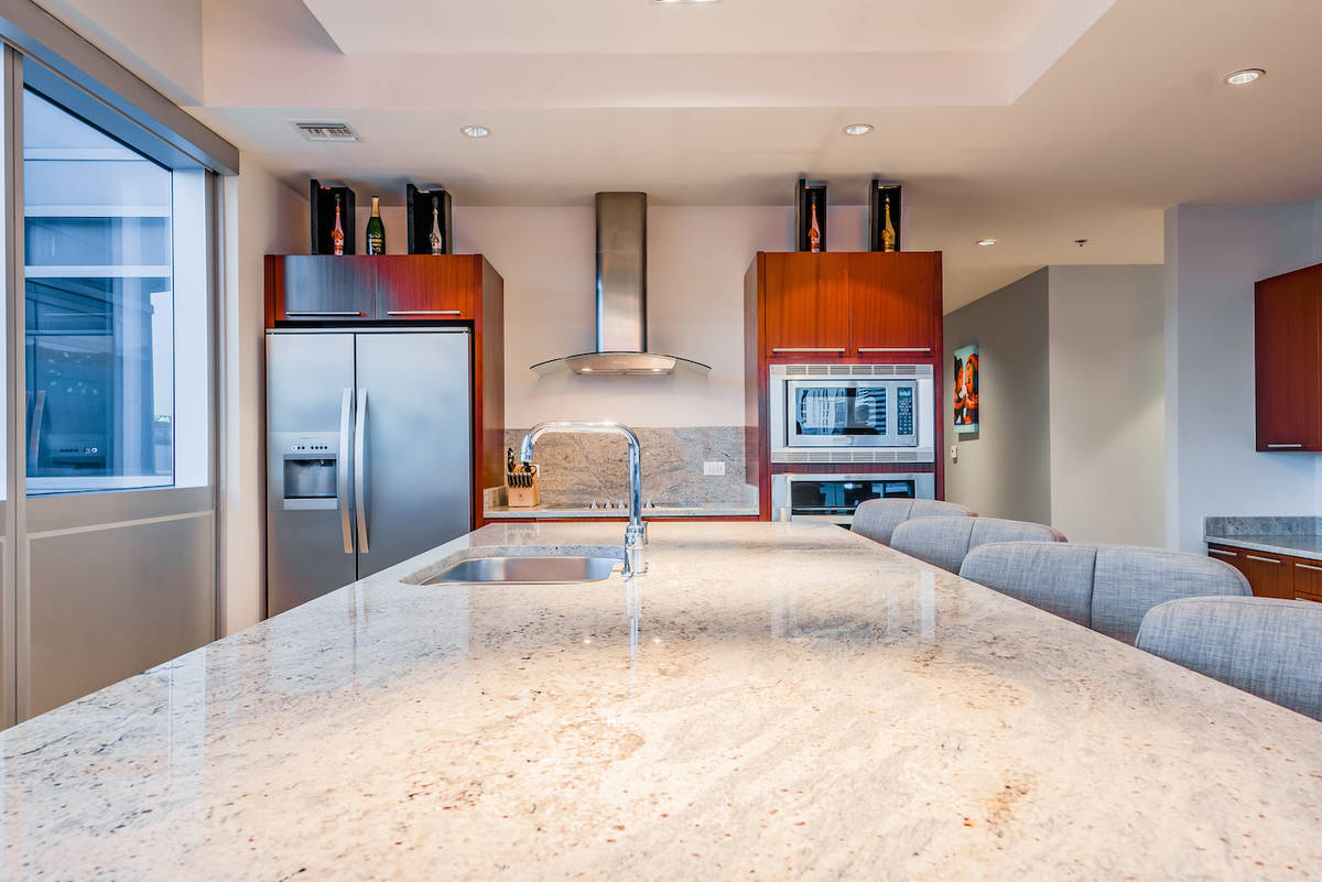 The kitchen showcases an expansive central Kashmir granite island. (Red Luxury Real Estate)