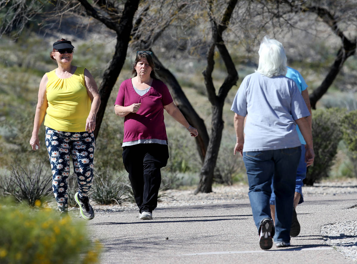 Rebecca Rovere, left, and Andrea Palmer pass Mary Scharn, 84, right and Barbara Cots, 70, while ...