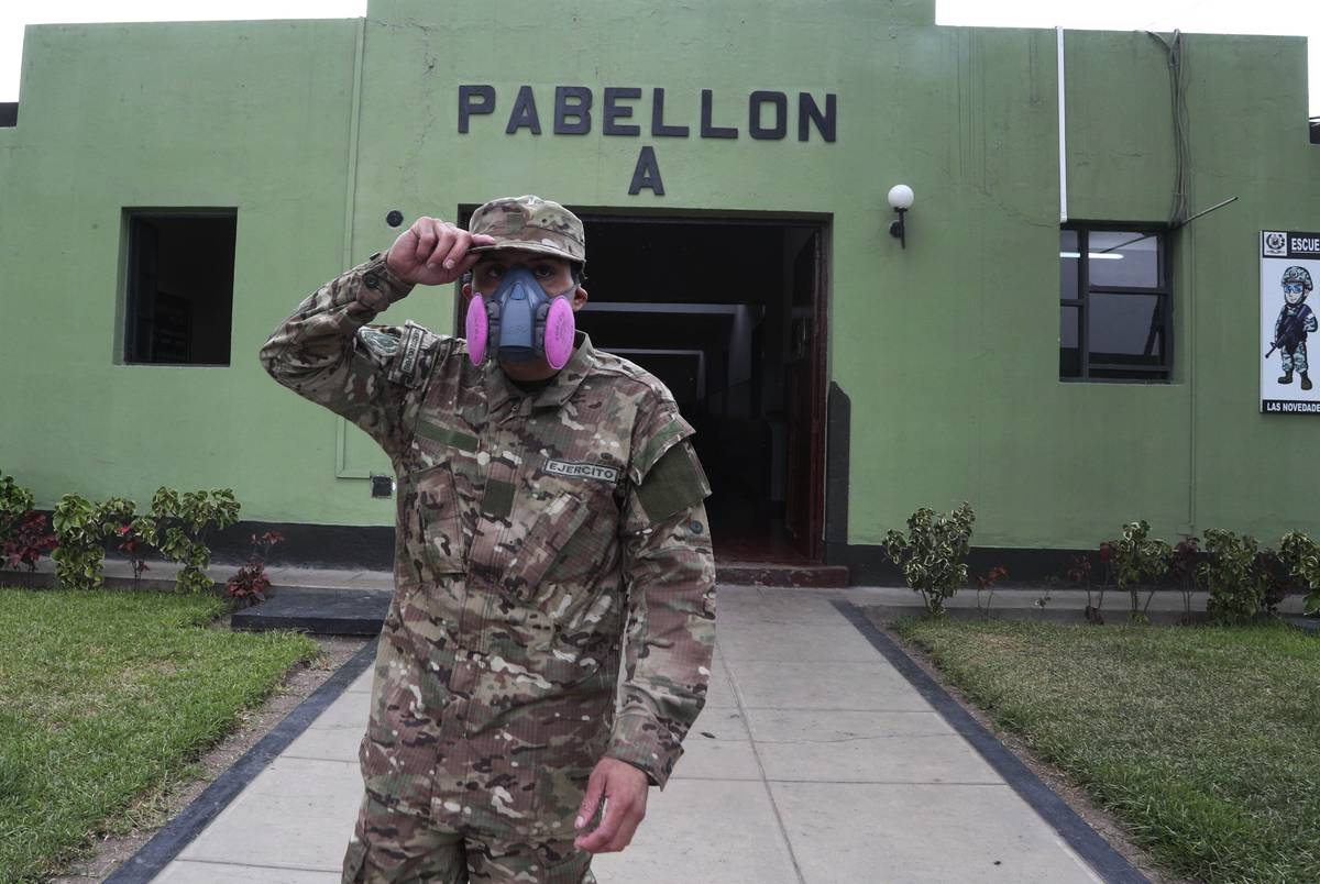 Wearing a face mask he brought from home, a military reservist stands outside his sleeping barr ...