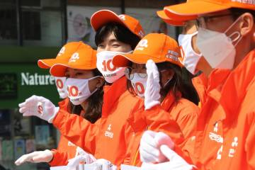 Supporters of the minor opposition People's Party wear face masks to help protect against the s ...