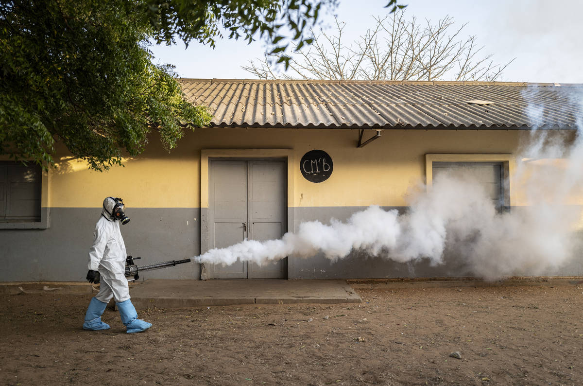 In this Wednesday, April 1, 2020, photo, a municipal worker sprays disinfectant at a school to ...