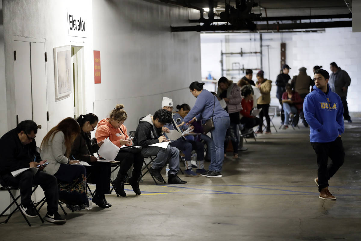 Unionized hospitality workers wait in line in a basement garage to apply for unemployment benef ...