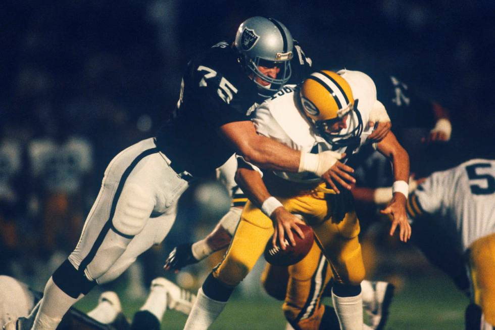 Los Angeles Raiders Hall of Fame defensive end Howie Long (75) sacks Green Bay Packers quarterb ...
