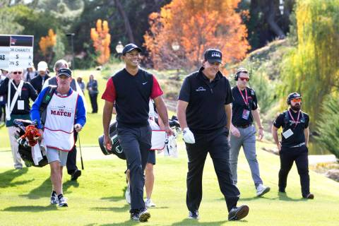 Tiger Woods, left, and Phil Mickelson walk to the fairway after teeing off from the first durin ...