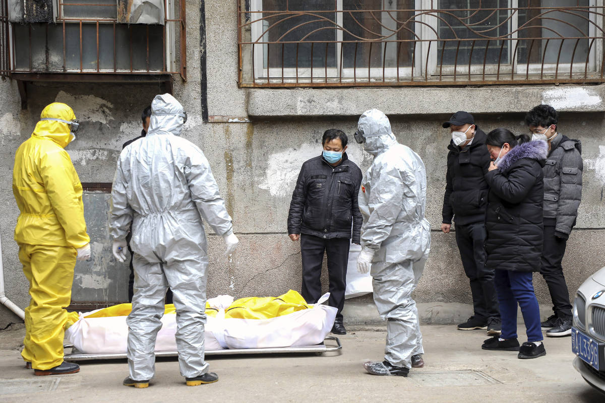 FILE - In this Feb. 1, 2020, file photo, funeral home workers remove the body of a person suspe ...