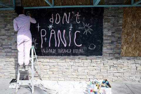 Artist Mila May paints her mural on a boarded up window of Retro Vegas on Main Street in downto ...