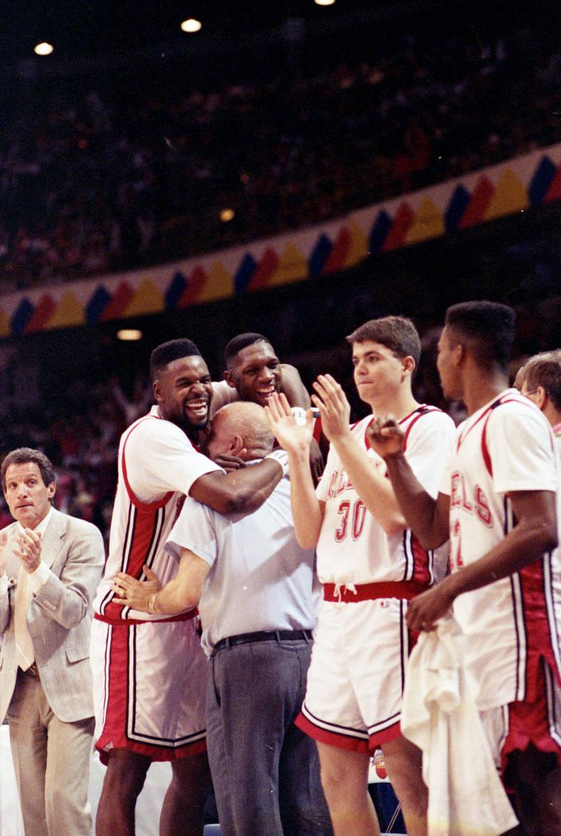 UNLV Rebels player Mosses Scurry and David Butler hug head coach Jerry Tarkanian after winning ...