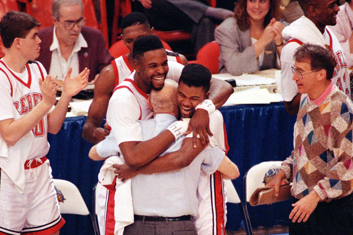 UNLV players Moses Scurry, left, and Anderson Hunt hug their coach Jerry Tarkanian after their ...