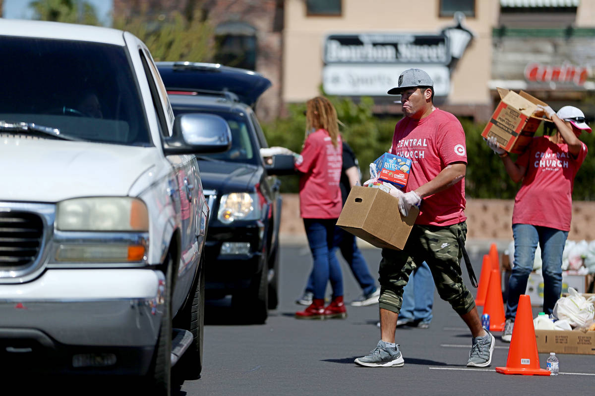 Volunteers for Three Square Food Bank give out food at Palace Station Casino in Las Vegas, Thur ...