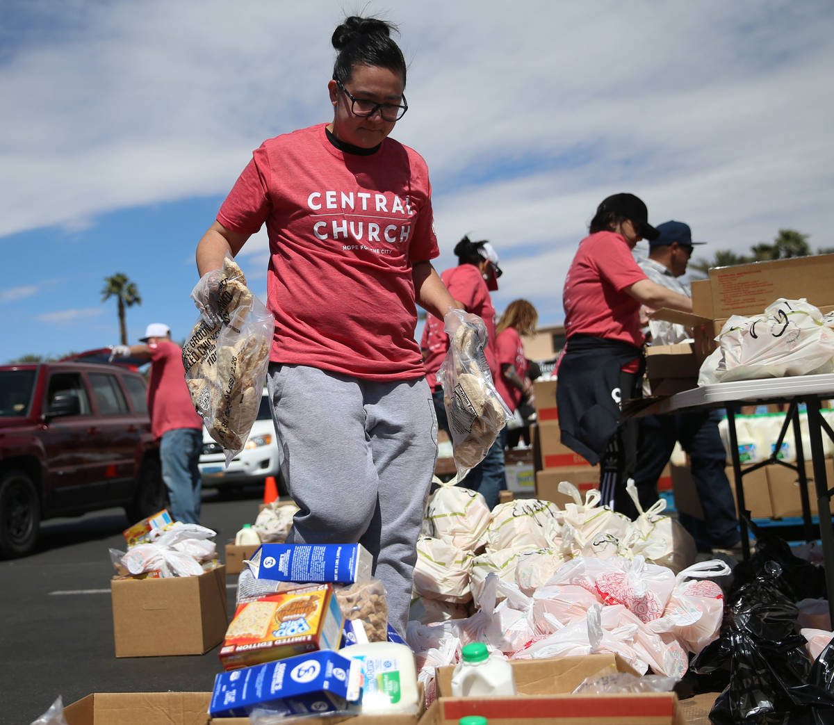 Three Square Food Bank volunteer Courtney Ford organizes boxes of food to give out at Palace St ...