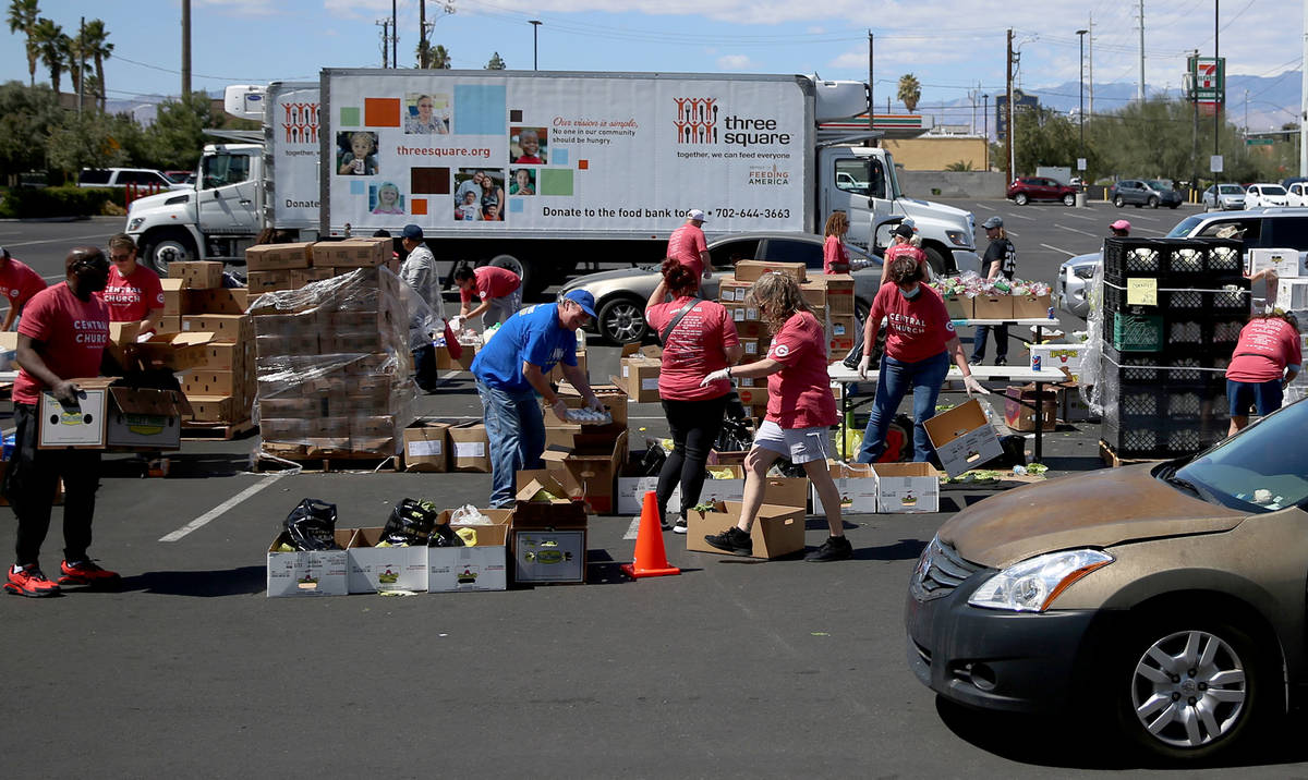Volunteer with Three Square Food Bank give out food at Palace Station Casino in Las Vegas, Thur ...