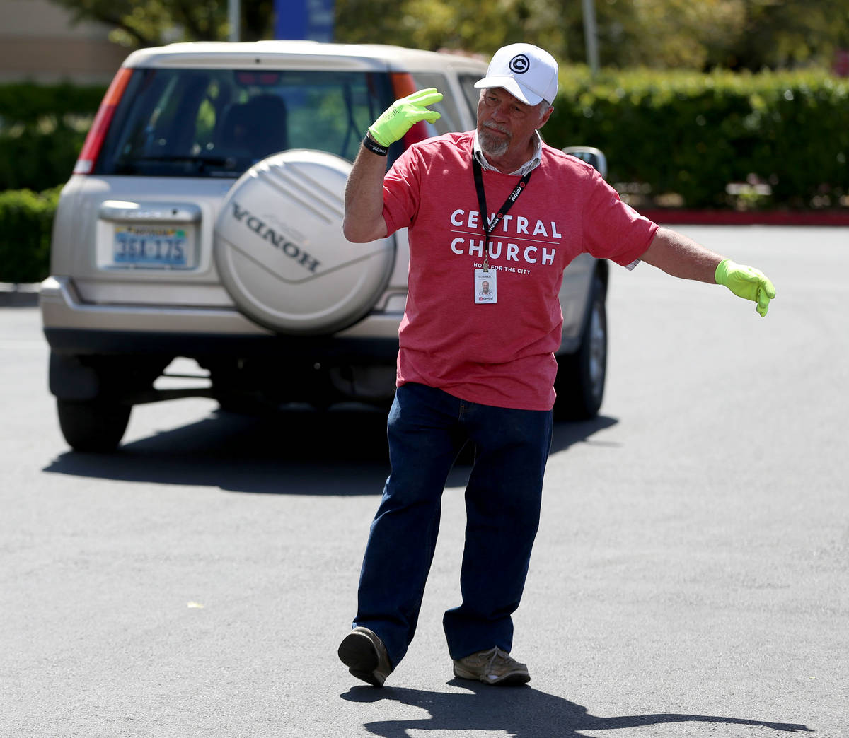 Three Square Food Bank volunteer Norman Fultz directs people in their cars waiting to receive f ...