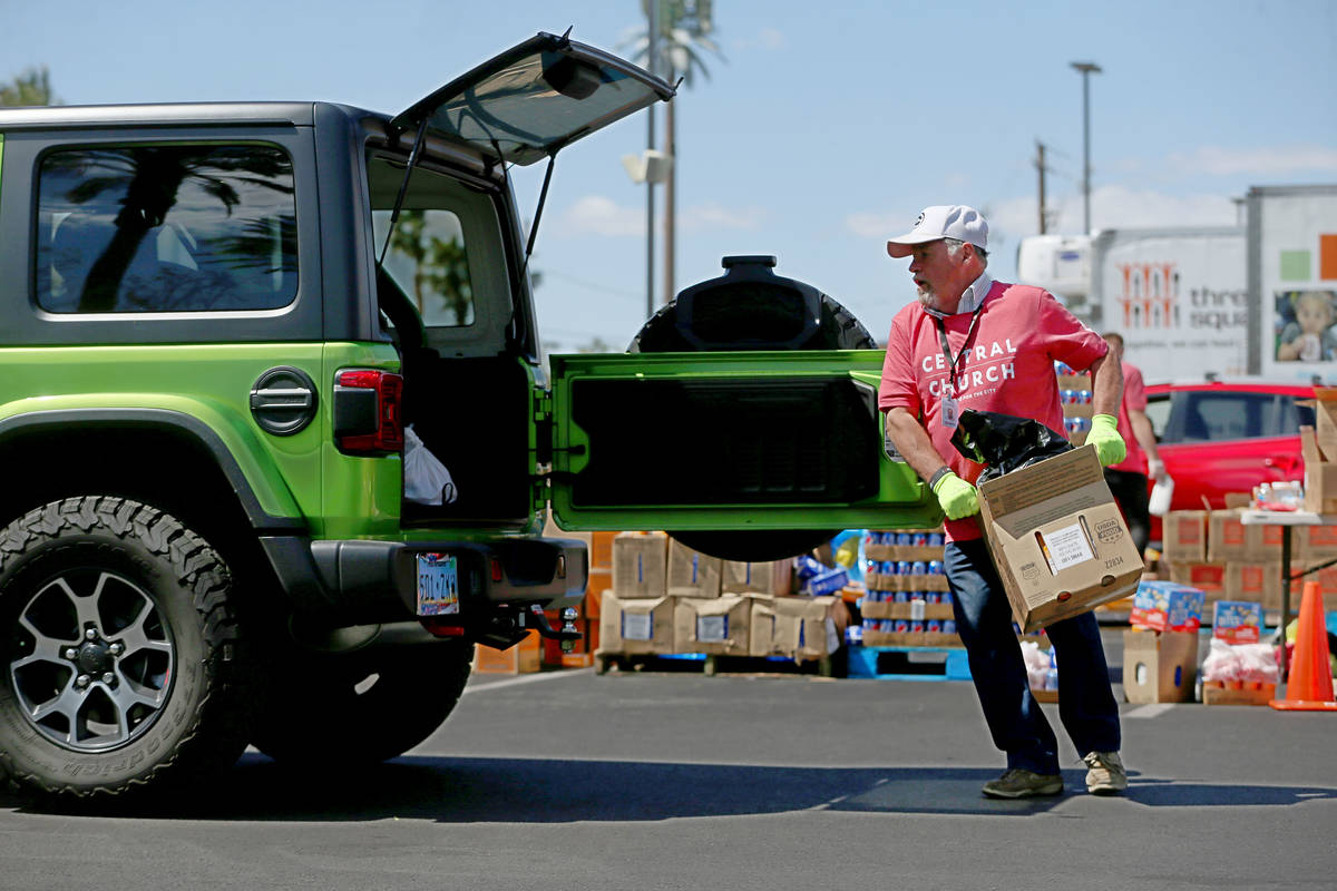 Three Square Food Bank volunteer Norman Fultz hands out food to people in their cars at Palace ...