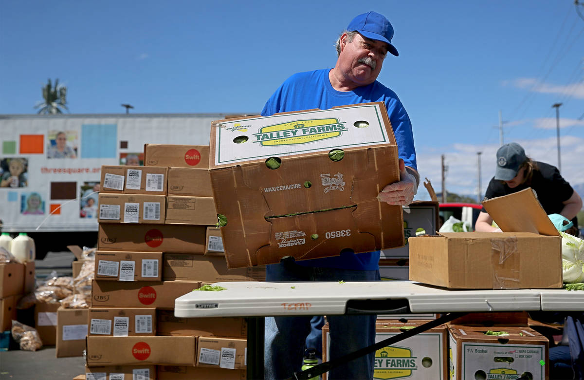 Three Square Food Bank volunteer John Castillo organizes food to give out at Palace Station Cas ...