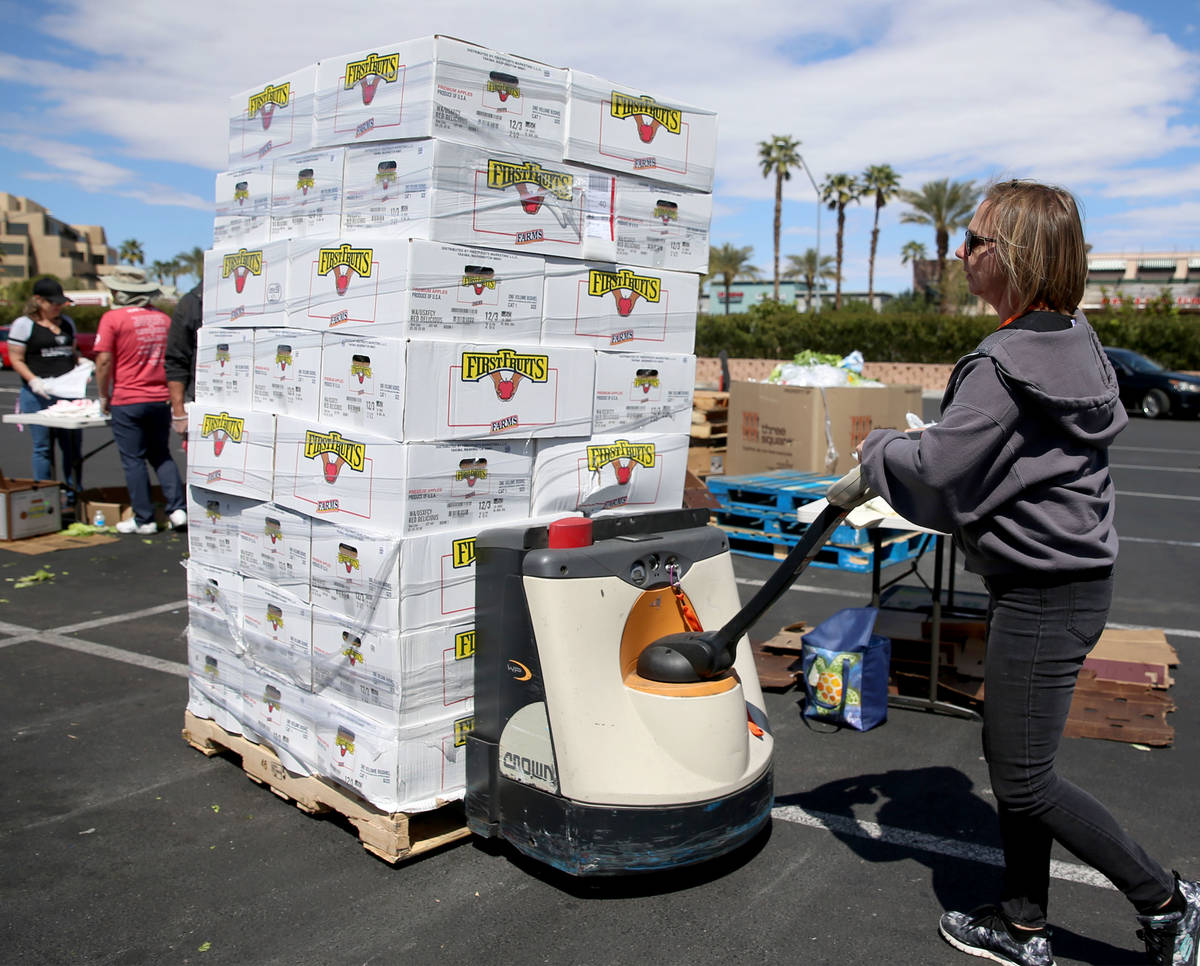 Three Square Food Bank warehouse assistant Kari Guerrero moves boxes of fresh fruit to give out ...