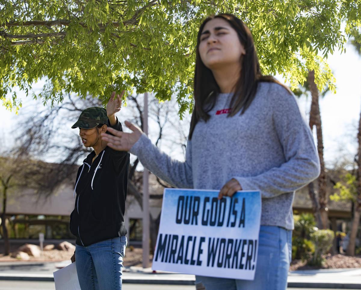 Crystal Espinoza, left, and Dariahne Navarro, 16, right, pray with family and friends for Adria ...