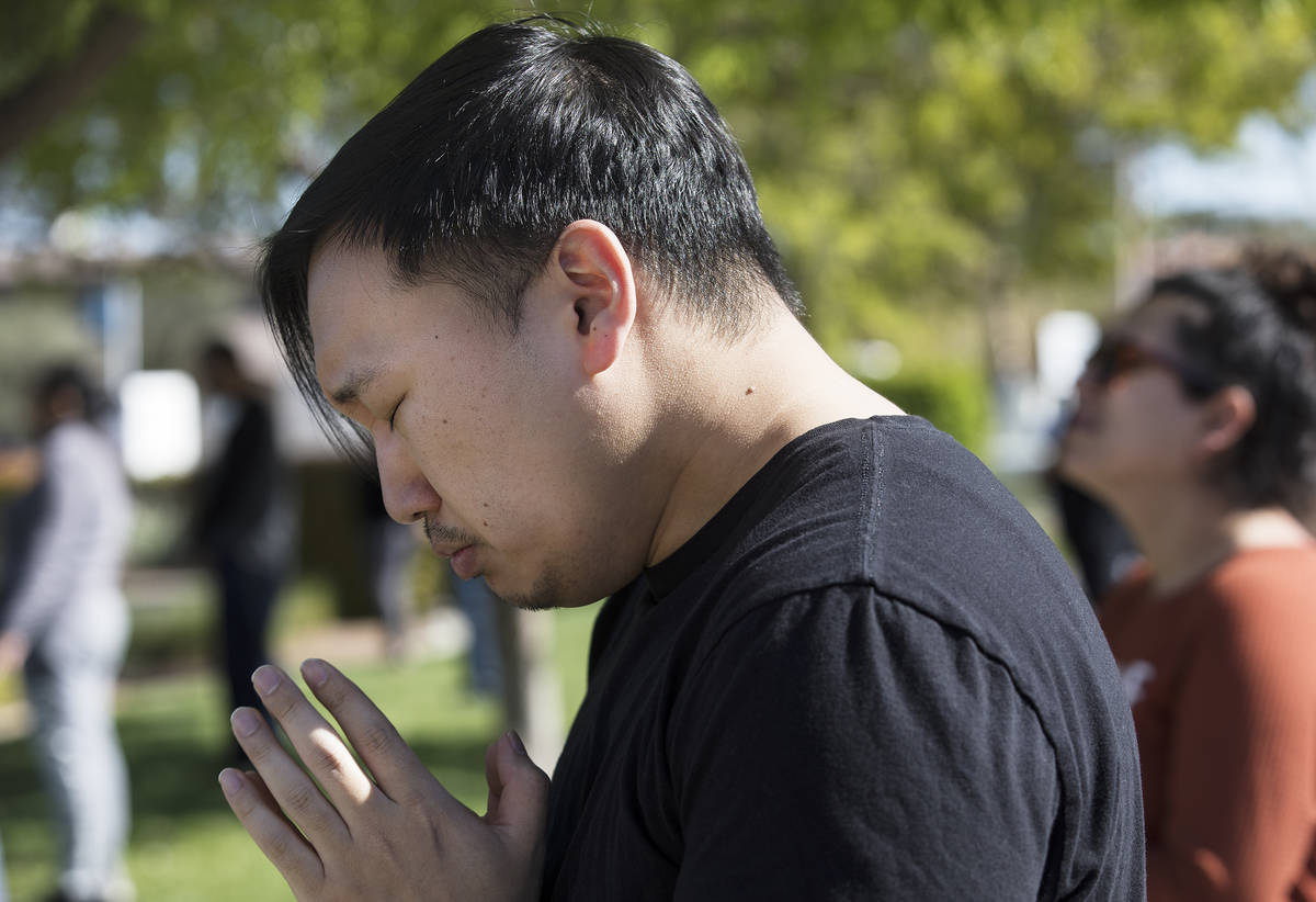 Paul Kim prays with family and friends for his friend Adriana Huh who is in the hospital with a ...