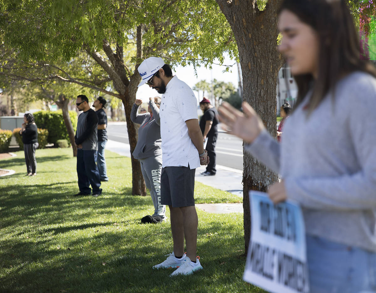 Haz Leon, center, prays with family and friends for his friend Adriana Huh who is in the hospit ...