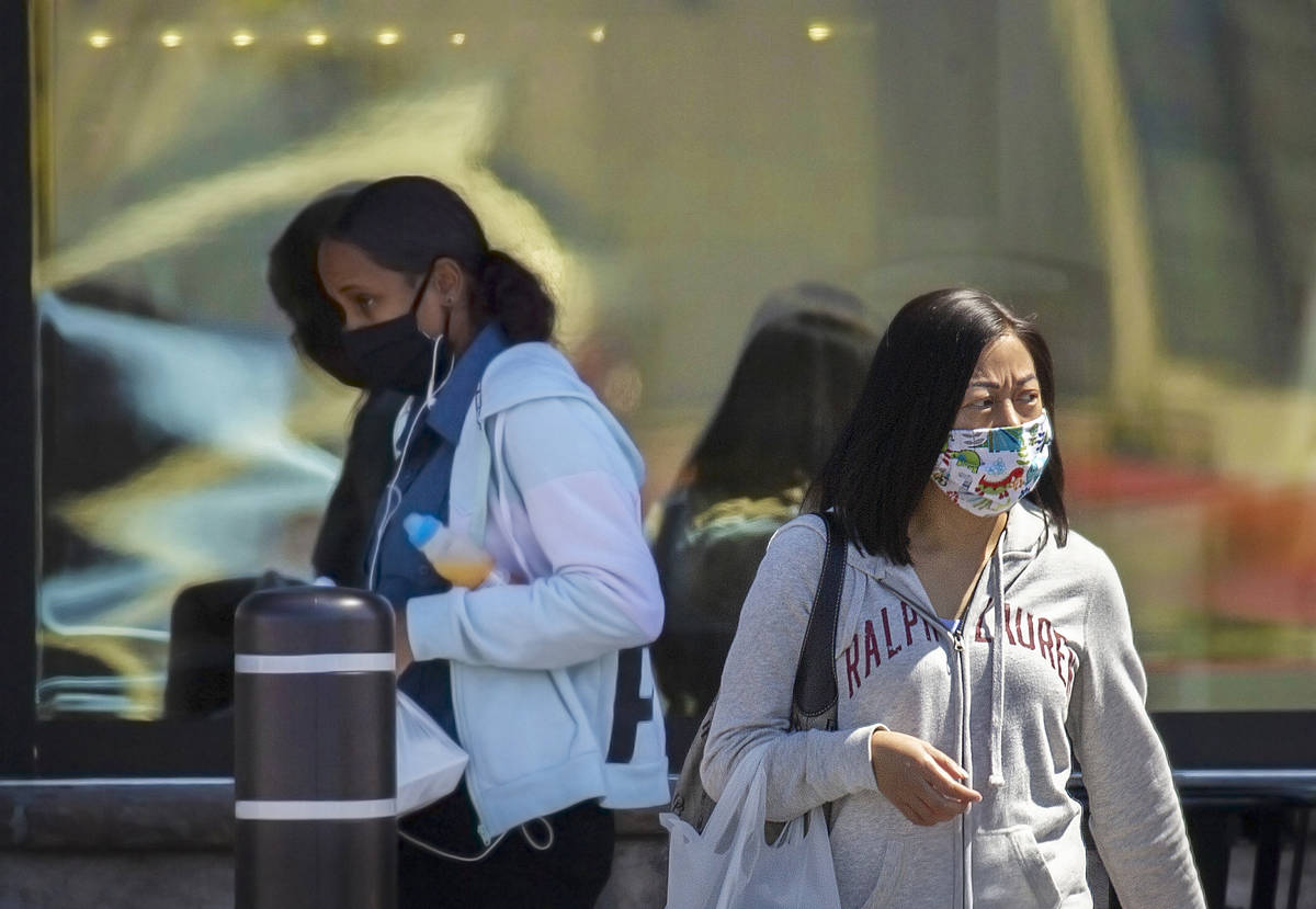Shoppers wear protective masks outside Albertsons at North Hualapai Way in the northwest valley ...