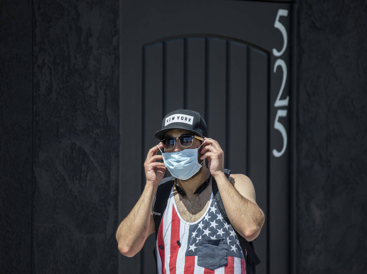 Jesse Cintron puts on a protective mask in downtown Las Vegas on Friday, April 3, 2020. (Benjam ...