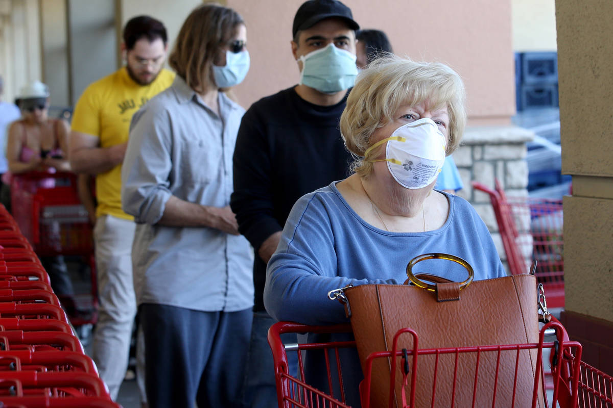 Shoppers, including Eileen Frey of Las Vegas, right, wear masks while waiting in line at Trader ...