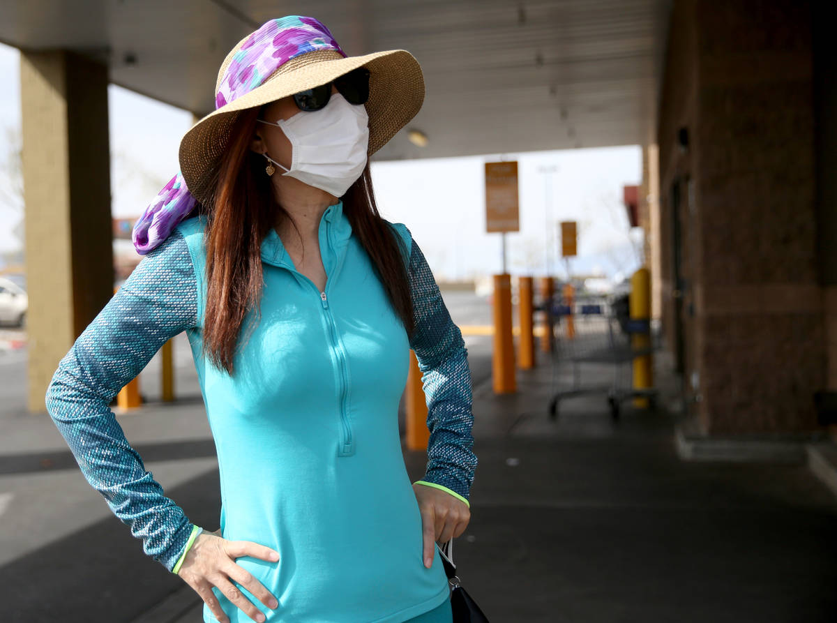 Heather Neil, 55, of Las Vegas, dons a mask while shopping at Sam's Club in southwest Las Vegas ...