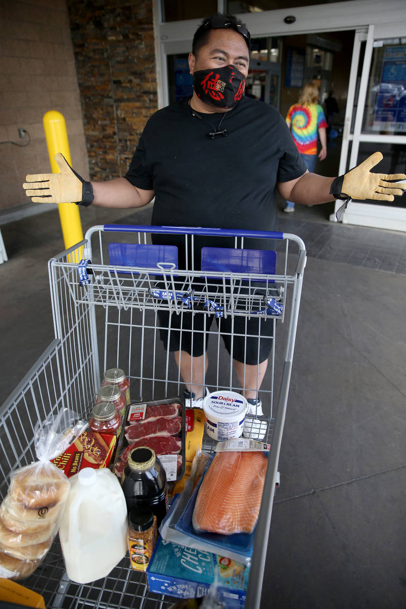 Sheffield Abella, 50, of Las Vegas, dons a mask while shopping at Sam's Club in southwest Las V ...