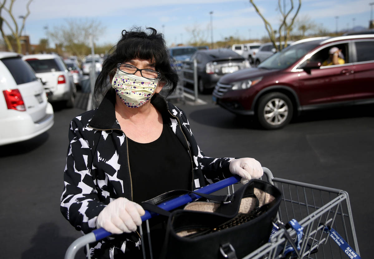 Zlata Petrouic, 60, of Las Vegas, dons a mask while shopping at Sam's Club in southwest Las Veg ...