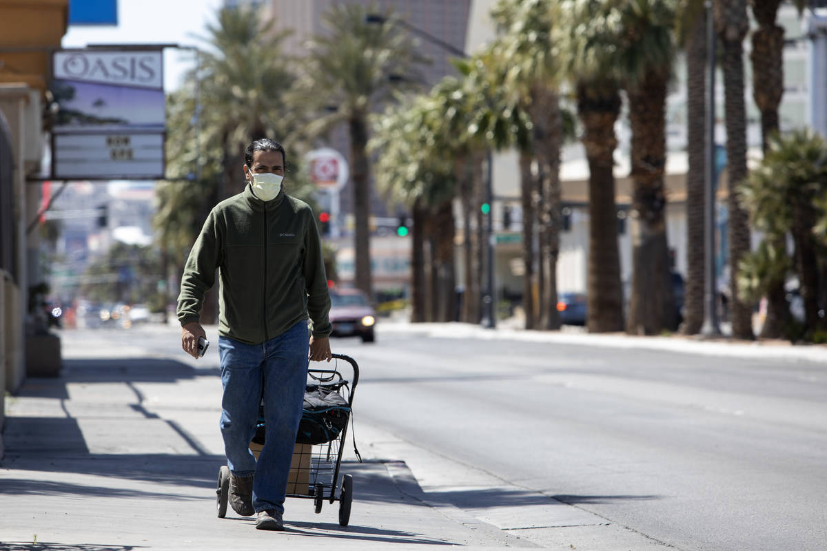 Jason Morciglio walks down Las Vegas Boulevard wearing a mask to protect himself from COVID-19 ...