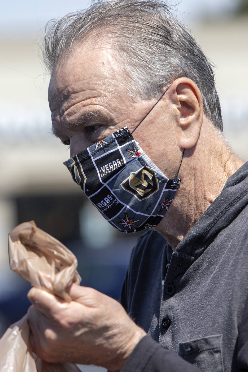 Michael McGowan wears a mask made out of Vegas Golden Knights fabric as he loads his car in the ...