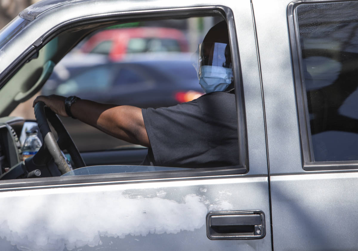 A driver wears a mask and face shield in the parking lot of the Smith's Food and Drug on South ...