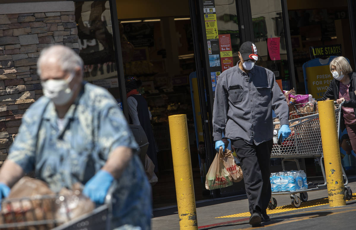 Masked shoppers exit Smith's Food and Drug on South Rancho Drive on Friday, April 3, 2020, in L ...