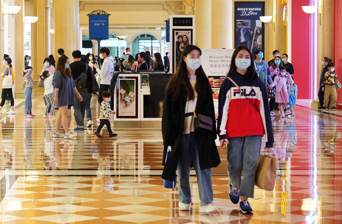 Shoppers wearing masks stroll through the Shoppes at Venetian on April 10, 2020 in Macao. (Insi ...