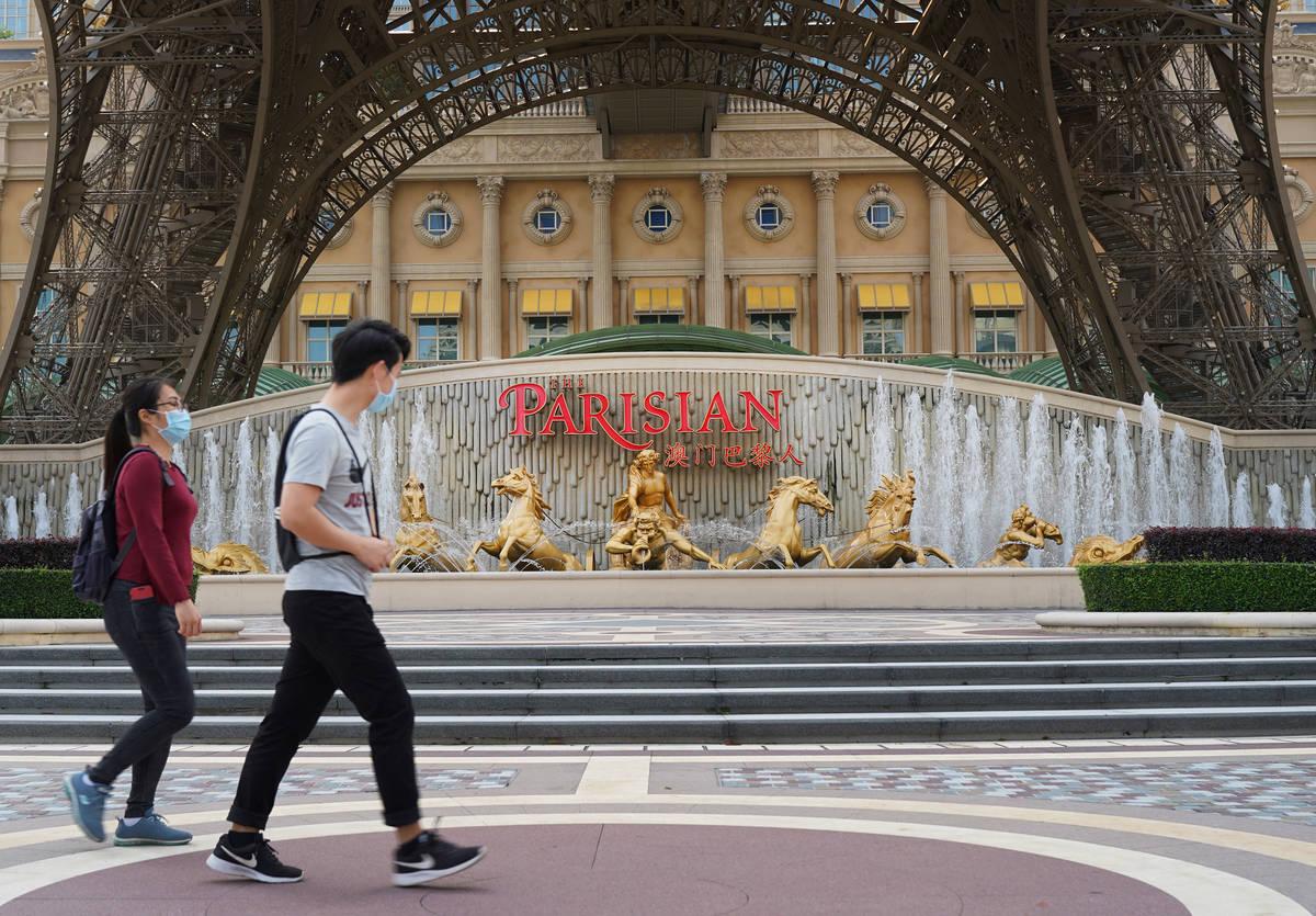 Orang-orang berjalan melewati replika Menara Eiffel di luar Parisian Macao pada 10 April 2020. (Di ...