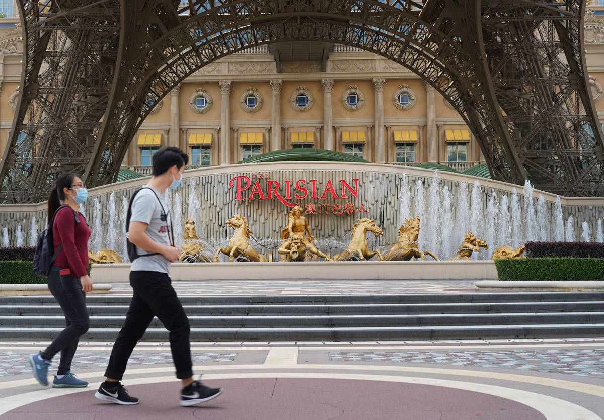 People walk past a replica Eiffel Tower outside the Parisian Macao on April 10, 2020. (Inside A ...