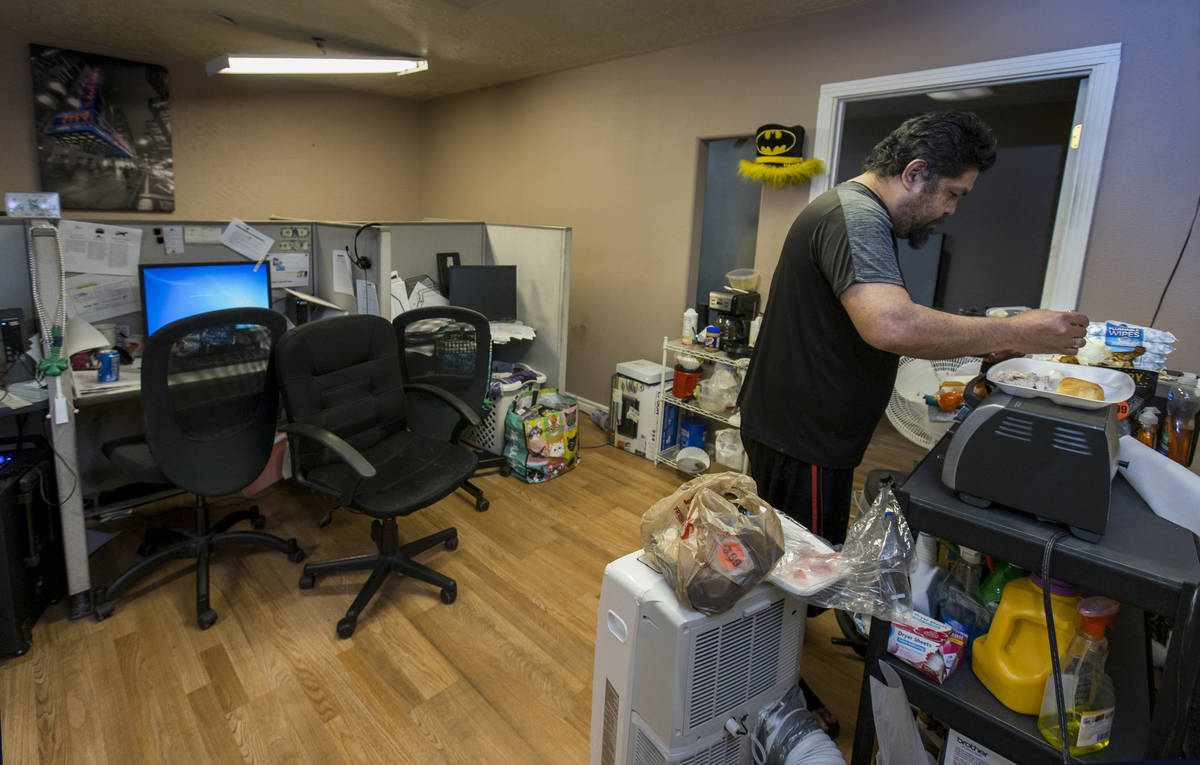 Jeremy Ferreira prepares some dinner for his family within a small office space they are tempor ...
